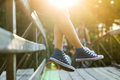 Young Woman Sitting On A Bridge Railing In Jeans Sneakers Stock Images - 75551644