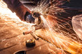Worker Cutting Metal With Grinder. Sparks While Grinding Iron. Stock Image - 75568691