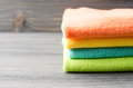 Colorful Bath Towels On Wooden Background Closeup Stock Photos - 75592393