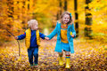 Kids Playing In Autumn Park Stock Photos - 75594113