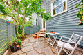Small Fenced Back Yard With Stone Floor And Chairs. Royalty Free Stock Image - 75605086