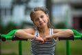 Little Girl Sitting On Exercise Equipment In The Public Park. Royalty Free Stock Photography - 75705937