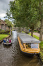 Tourists Steering A Boat Through The Canals Of Giethoorn Royalty Free Stock Photos - 75863948