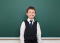 School Student Boy Posing At The Clean Blackboard, Grimacing And Emotions, Dressed In A Black Suit, Education Concept, Studio Phot Royalty Free Stock Photos - 75888128