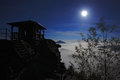 Night With Moon On The Lookout. White Fog In The Valley. Watchtower On The Stone Hill During Night. Night Landscape. Hills And Vil Stock Photos - 75945623