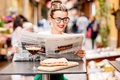 Woman Reading Newspaper At The Cafe Outdoors Stock Photography - 76002312