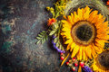 Sunflowers With Berries And Flowers. Floral Autumn Decoration On Dark Rustic Vintage Background Stock Photos - 76070833