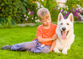 Kid And White Swiss Shepherd Dog Together On Green Grass Royalty Free Stock Images - 76073129