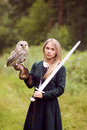 Girl In Medieval Dress Is Holding An Owl On Her Arm Royalty Free Stock Image - 76073376