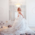 Young Beautiful Bride In Luxurious Wedding Dress. Huge Puffy Skirt With Train. Luxury Light Interior Royalty Free Stock Images - 76138669