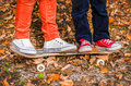 Feet In Sneakers On A Skateboard Two Children Autumn Stock Photo - 76150810