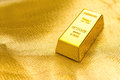 Piece Of Gold Bar On Golden Background Royalty Free Stock Photo - 76221355
