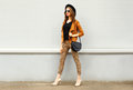 Fashion Pretty Young Woman Wearing A Retro Elegant Hat, Sunglasses, Brown Jacket And Black Handbag Walking In City Over Backg Royalty Free Stock Photo - 76405395