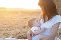 Beautiful Happy Mother Breastfeeding Her Baby Boy Outdoor. Royalty Free Stock Photography - 76419977