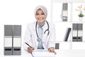 Asian Female Doctor With Stethoscope Smiling While Writing Down Stock Photography - 76463462