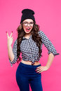 Close Up Studio Portrait Of Cheerful Blonde Hipster Girl Going Crazy Making Funny Face And Showing Her Tongue. Pink Wall Royalty Free Stock Images - 76511939