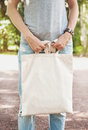 Woman Holding Empty Canvas Bag. Template Mock Up Royalty Free Stock Photo - 76624705