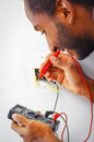Man Wearing White And Blue Shirt Working On Electrical Wall Socket Wires Using Multimeter, Electrician Concept Royalty Free Stock Image - 76674276