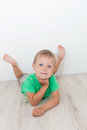 Little Handsome Boy With Blue Eyes Lying On The Floor Royalty Free Stock Photography - 76713827