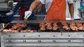 Gloved Hand Turning Meat Grilling On Large BBQ Stock Photos - 76715833