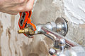 Plumber Fixing Water Tap Valve In Kitchen, Users Pliers Wrench. Royalty Free Stock Photo - 76724115