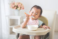 Baby Girl Sitting On High Chair And Feed Her Self Stock Photo - 76731470