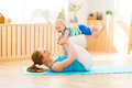 Sports Mother Is Engaged In Fitness And Yoga With Baby At Home Royalty Free Stock Images - 76752249