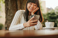 Happy Young Woman Using Her Cellphone At Cafe Royalty Free Stock Photography - 76785337