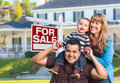Young Family In Front Of For Sale Sign And House Stock Photo - 76803270