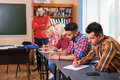 Student Group Write Test, Professor Observing, Young Diverse People Sit Desk University Classroom Examination Royalty Free Stock Images - 76832739