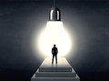 Man Standing On A Step In Front Of A Huge Light Bulb Royalty Free Stock Image - 76873346