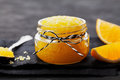 Orange Body Scrub With Sugar And Coconut Oil In Glass Jar On Black Table. Homemade Cosmetic For Peeling And Spa Care Stock Photography - 76892212