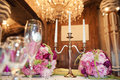 Gorgeous Flower Arrangement At The Wedding Table. And Candleholder For Three Candles On The Background Of Chandeliers Royalty Free Stock Photo - 76938515