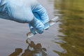 Sample Water From The River For Analysis. Hand In Glove Holding Stock Photo - 76991120