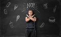 Muscled Young Man Showing Stop Sign With His Hands And Says No To Unhealthy Food On The Background Of Blackboard Stock Images - 77209954