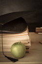 Teachers Desk With  Books Stacked, Mortarboard, Apple And Chalkb Stock Photography - 77220672
