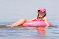 Sad Girl In A Cap Floating In River Sat On The Swimming Circle Royalty Free Stock Photos - 77292338