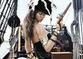 Profile Of A Sexy Pirate Female Captain Standing On The Deck Of Her Ship With Pistol In Hand. Royalty Free Stock Image - 77320856