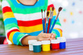 Child S Hands With Lots Of Brushes And Colorful Watercolors Royalty Free Stock Photos - 77381178