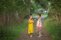 Little Girls Excitedly Talking Standing In The Green Alley. Royalty Free Stock Photography - 77455227