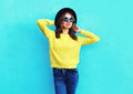 Fashion Pretty Woman Wearing Black Hat And Yellow Knitted Sweater Over Colorful Blue Royalty Free Stock Images - 77533489