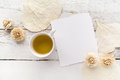 Flowers On White Wooden Table With Blank Pages And Cup Of Green Tea. Free Space For Text. Top View Stock Photos - 77569843