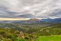 Paraglider Flying Over The Green Mountains Around Cape Town, South Africa. Winter Season, Cloudy And Dramatic Sky. Unrecognizable Stock Photos - 77571123