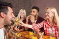 People Group Eating Fast Food Burgers Sitting At Wooden Table In Cafe Royalty Free Stock Photo - 77588495