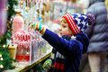 Little Kid Boy With Candy Cane Stand On Christmas Market Stock Photo - 77592830