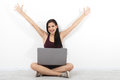 Happy Young Woman Sitting On Floor With Crossed Legs And Using Laptop On White Background Royalty Free Stock Photo - 77656365