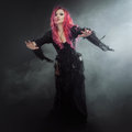 Halloween Witch Creates Magic. Attractive Woman With Red Hair In Witches Costume Standing Outstretched Arms, Strong Wind Royalty Free Stock Image - 77682286