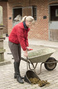 Woman Mucking Out In A Stable Yard Stock Images - 77703484
