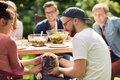 Happy Friends Having Dinner At Summer Garden Party Stock Images - 77726014