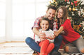 Family Gathered Around A Christmas Tree, Using A Tablet Stock Images - 77851444
